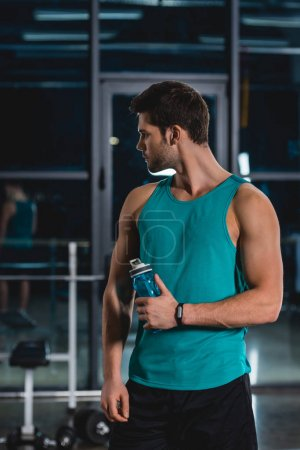 sportsman with fitness tracker holding bottle of water in sports center
