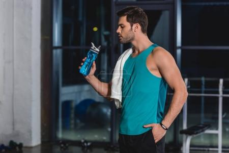 tired sportsman with towel drinking water from sport bottle in gym