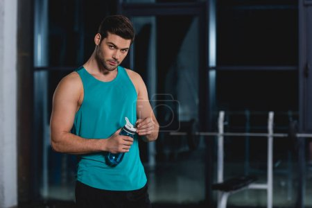 Photo for Sportsman holding sport bottle with water in gym - Royalty Free Image