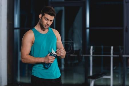 Photo pour Sportsman tenant bouteille sport avec de l'eau dans la salle de gym - image libre de droit