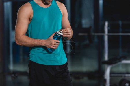 Photo for Cropped view of sportsman holding sport bottle with water in gym - Royalty Free Image