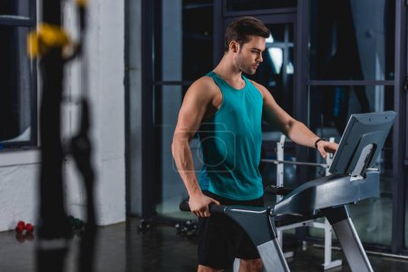 Photo for Handsome sportsman training on treadmill in gym - Royalty Free Image