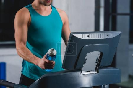 cropped view of sportsman with sport bottle training on treadmill in gym