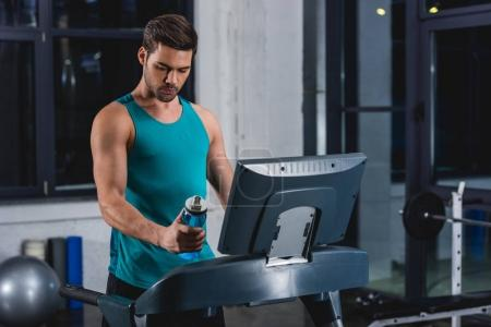 sportsman holding sport bottle while jogging on treadmill in gym