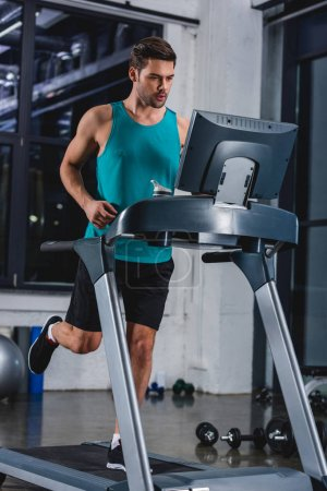 athletic man running on treadmill in sports center