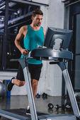 athletic man running on treadmill in sports center