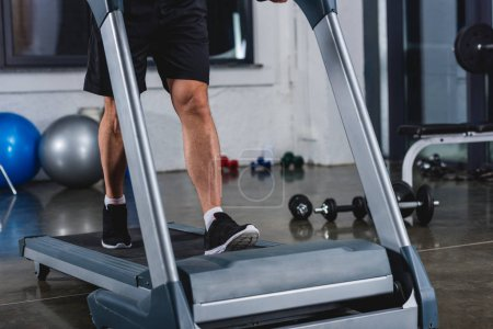 low section view of sportsman in sneakers jogging on treadmill in gym