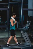 tired sportsman with towel training on treadmill in gym