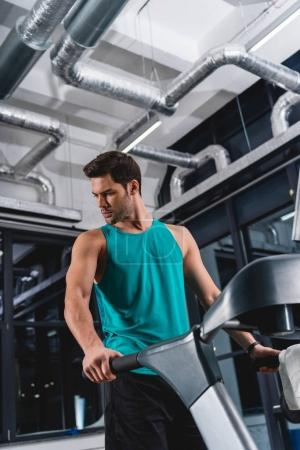 handsome sportsman exercising on treadmill in gym