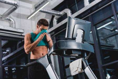 sweaty sportsman training on treadmill in gym
