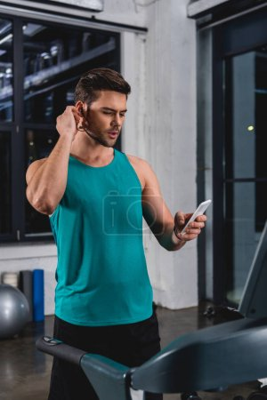 sportsman listening music with earphones and smartphone while exercising on treadmill in gym