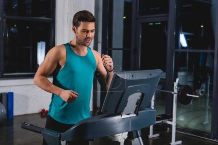 sportsman jogging on treadmill in sports hall