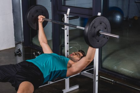 strong sportsman exercising with barbell in gym
