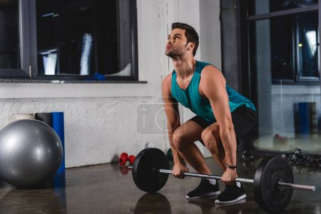 strong sportsman training with barbell in sports hall