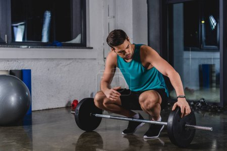 Photo for Handsome sportsman with barbell in sports hall - Royalty Free Image