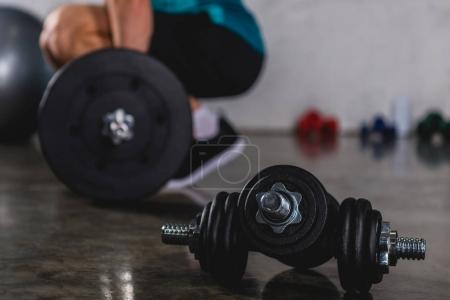sportsman training with barbell, dumbbells lying on floor on foreground