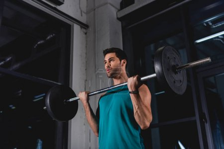 sportsman lifting barbell during cross training in gym