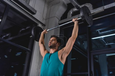 strong sportsman lifting barbell during cross training in gym