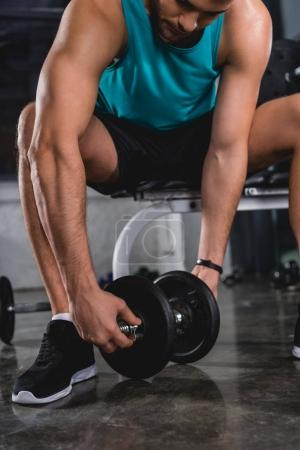 muscular sportsman exercising with dumbbell in sports center