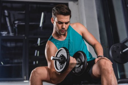strong muscular sportsman lifting dumbbell in gym