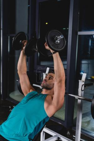 muscular sportsman exercising with dumbbells in gym