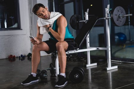 sweaty sportsman with towel resting and using smartphone in gym