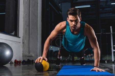 muscular sportsman doing push ups with medicine ball on yoga mat in sports center