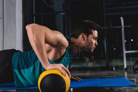 sportsman doing push ups with medicine ball on mat in sports hall