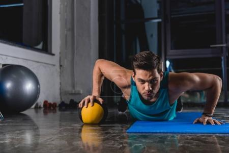 sportsman doing push ups with medicine ball on yoga mat in gym