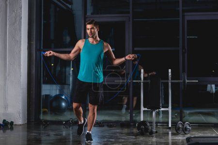 sportsman jumping with skipping rope in gym