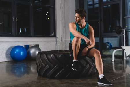 sportsman sitting on tire in sports center