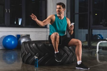 sportsman sitting on tire and using smartphone in gym