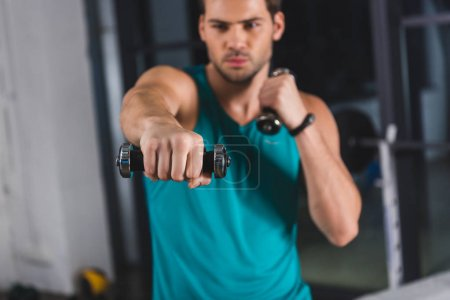 selective focus of sportsman exercising with dumbbells in sports center