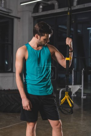 sportsman standing with suspension straps in gym