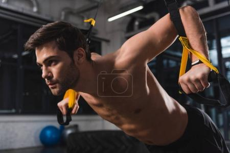 shirtless sportsman training with suspension straps in gym