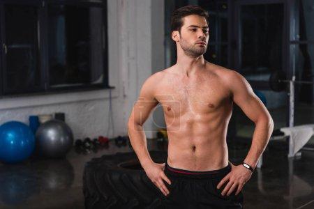 shirtless muscular sportsman posing in gym