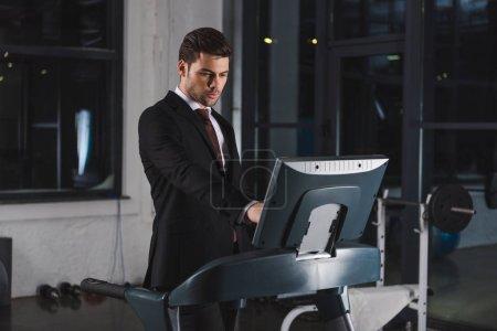Photo pour Bel homme d'affaires en costume formation sur tapis roulant dans le centre sportif - image libre de droit