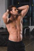 shirtless muscular sportsman posing in sports hall