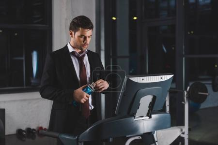 businessman in suit training on treadmill with bottle of water in sports center