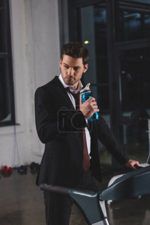 manager in suit training on treadmill with sport bottle in gym