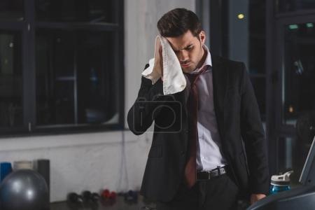 Photo pour Fatigué en sueur homme d'affaires avec la serviette au centre sportif - image libre de droit