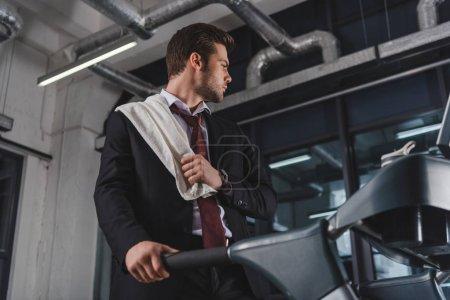 Photo pour Homme d'affaires fatigué avec formation serviette sur tapis roulant dans la salle de sport - image libre de droit
