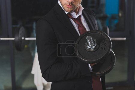 cropped view of sporty businessman in suit training with dumbbell in gym