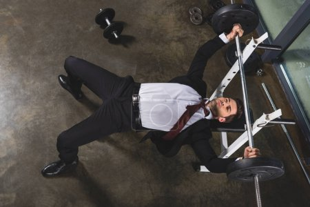 Photo for Businessman in suit training with barbell in sports center - Royalty Free Image