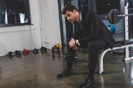 tired businessman in suit with fitness tracker sitting in gym with dumbbells