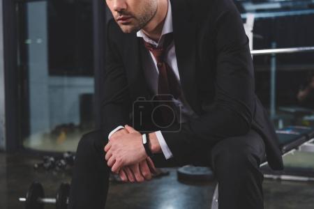 Photo pour Vue recadrée de l'homme d'affaires fatigué en costume avec tracker de fitness assis dans la salle de gym - image libre de droit