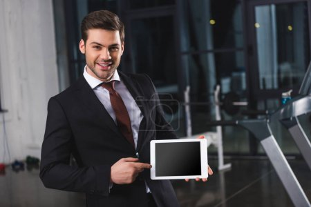smiling businessman in suit pointing at digital tablet in sports center