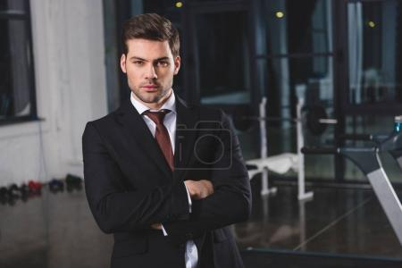 confident businessman in formal wear with crossed arms in gym