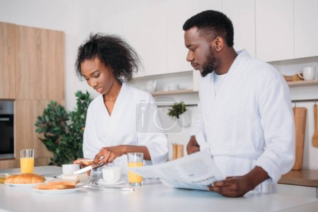 Young woman spreading butter on toast while man standing with newspaper in kitchen