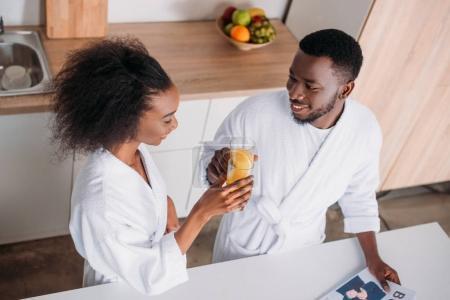 Photo pour Vue d'angle élevé de couple tinter les verres de jus d'orange dans le matin - image libre de droit